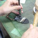 自社工場では、鋲打ちやバックルピンの穴あけなどが手作業で進められている。