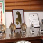 商談室の一角には、ランドセル作りの実績をたたえた賞状やトロフィーが数多く並ぶ。