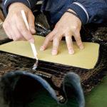 型紙に沿って断裁用の印をつける革出しの作業は、長年の経験を要する。